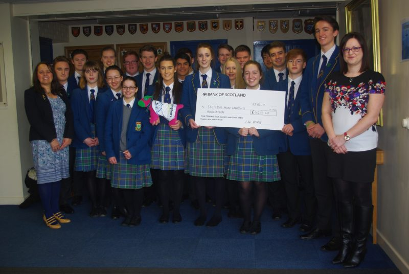 SHA community fundraiser, Linda Winters (left) and youth team leader Kirsten Walker picks up a cheque for £4453 from the High School of Glasgow's Law House